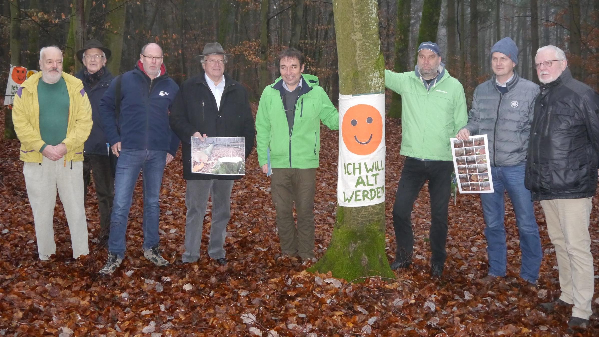"""Vertreter von Umweltverbänden bei einer Pressekonferenz im Steigerwald. Acht Männer stehen neben Bäumen. An einem Baum hängt ein Schild mit der Aufschrift """"Ich will alt werden""""."""