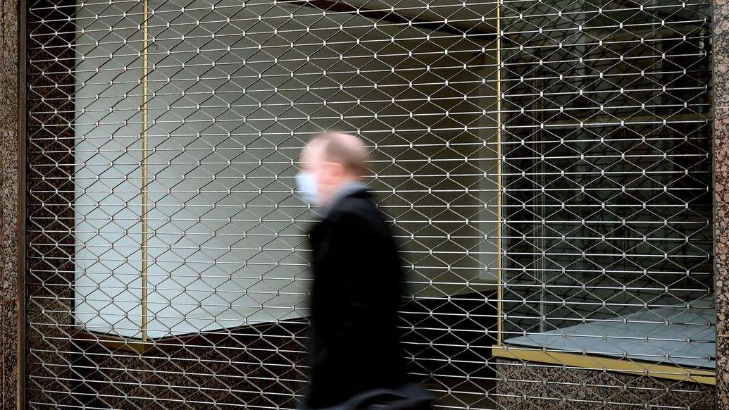 Ein Mann läuft an einem geschlossenen Laden vorbei