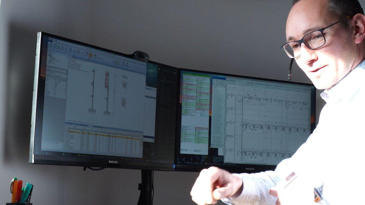 Mann sitzt mit Headset vor zwei Computer-Bildschirmen