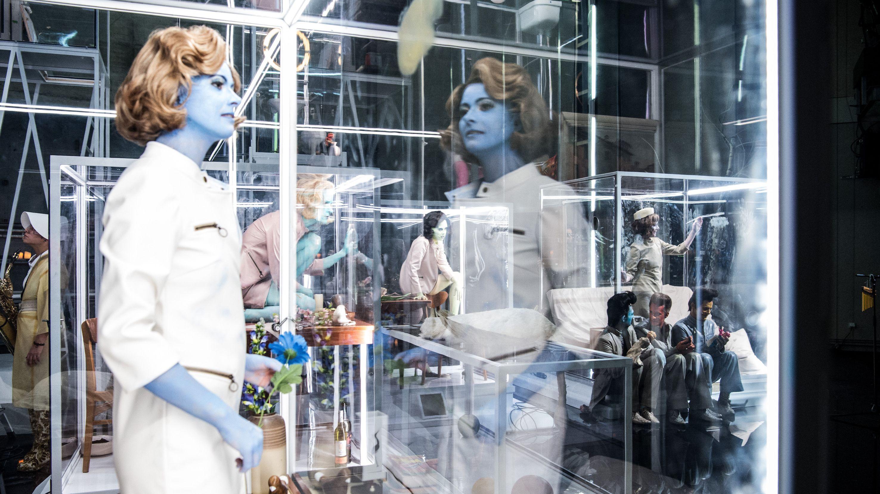 Auf der Bühne sind mehre weibliche Darstellerinnen in Glaskästen zu sehen. Sie wirken wie Schaufensterpuppen.