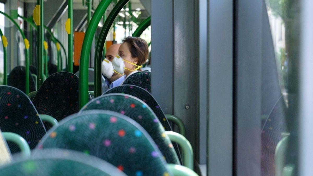 Jose und Marina Almeida sitzen mit Shutzmasken in einem leeren Bus