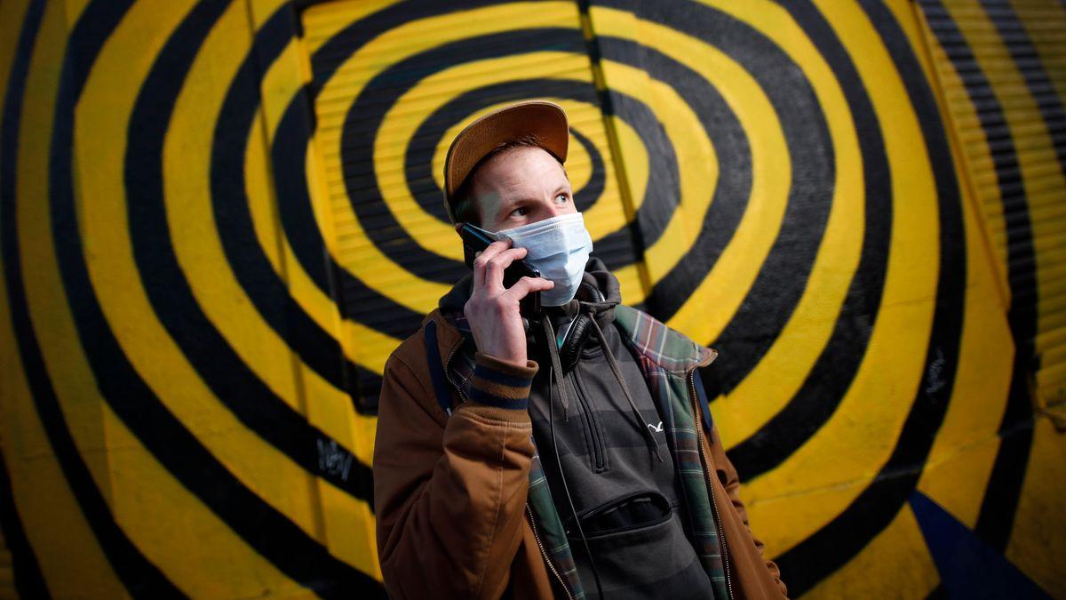 Ein Passant mit Mundschutz posiert mit seinem Handy in Köln