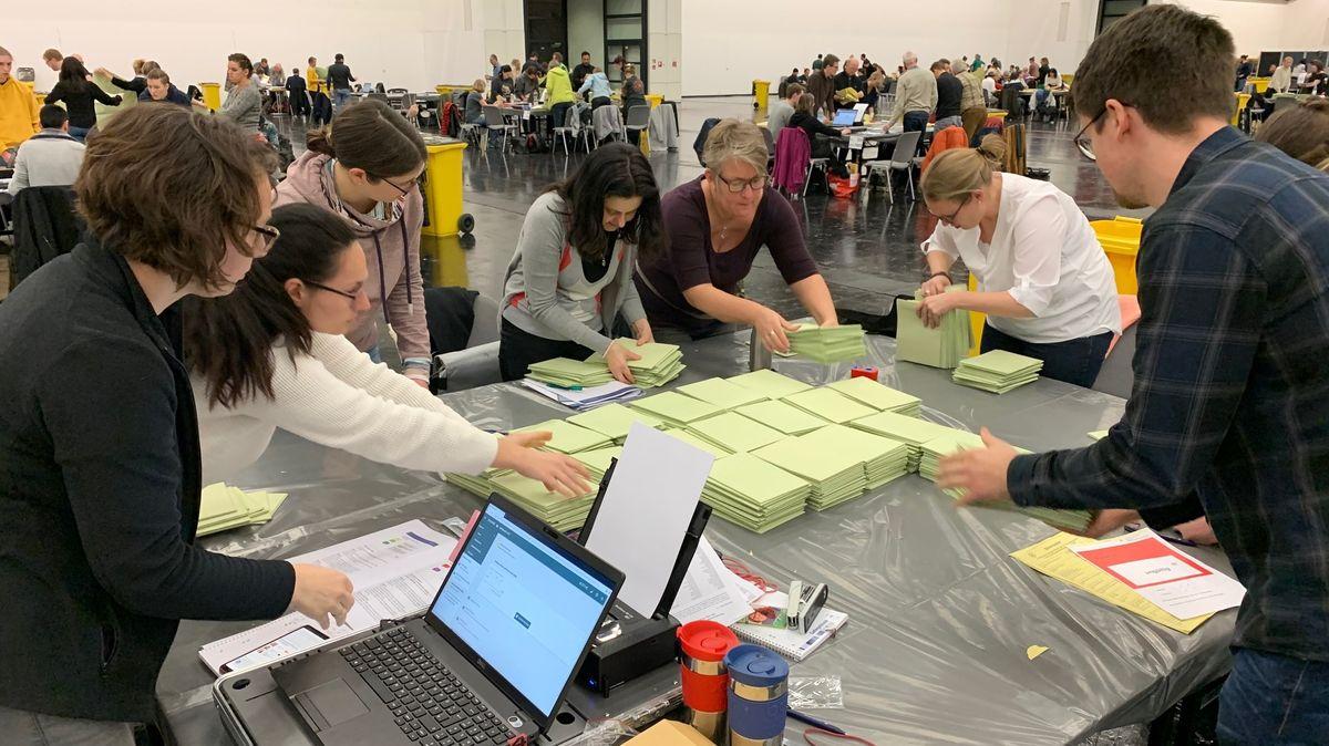 Blick auf einen Tisch, an dem mehrere Wahlhelfer grüne Stimmzettel auszählen und das Ergebnis in einen Computer eintragen.