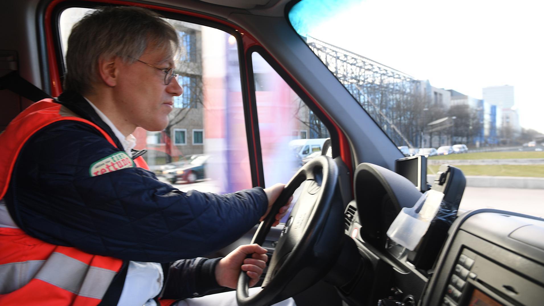 Ein Tierarzt sitzt am Steuer eines Tierrettungswagens und fährt durch München.