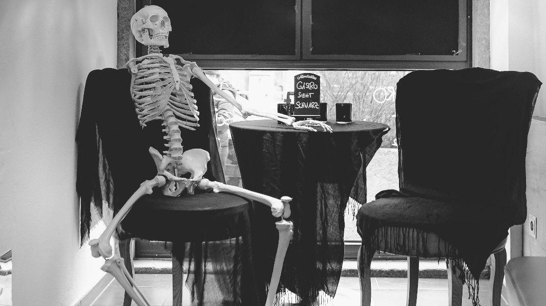 Skelett an Tisch in einem Eiscafé