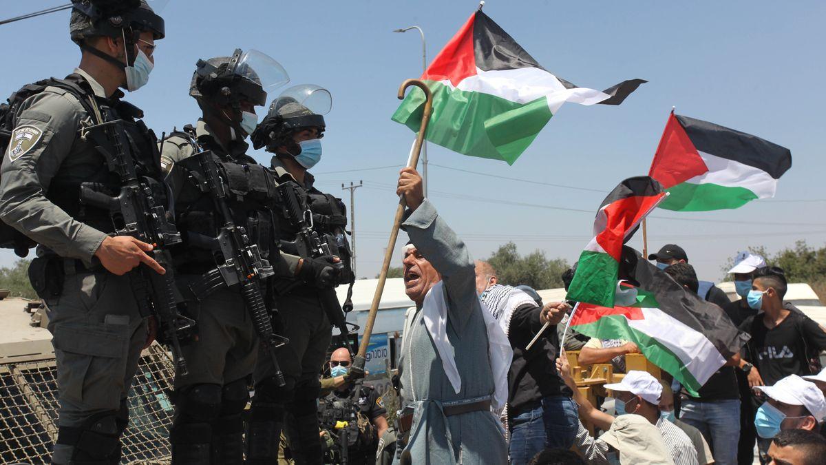 Palästinensische Demonstranten recken in Salfit (WestBank) israelischen Soldaten Fahnen entgegen und rufen dabei.