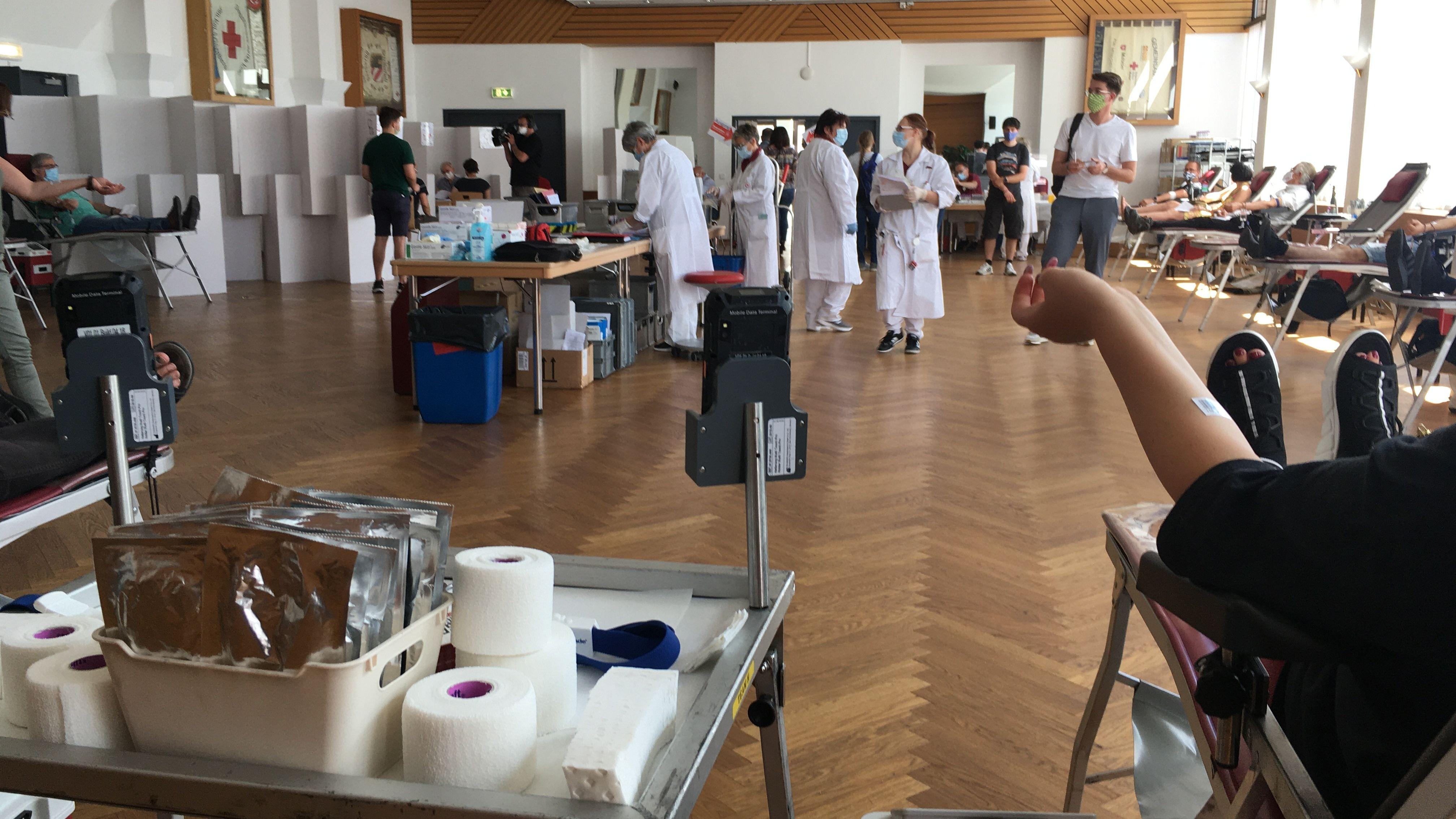 Viele Personen beim Blutspenden in einem großen Saal