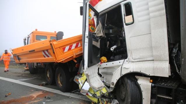 Die Führerkabine eines Lastwagens, der auf eine orangefarbenes Baustellenfahrzeug aufgefahren ist, ist schwer beschädigt.