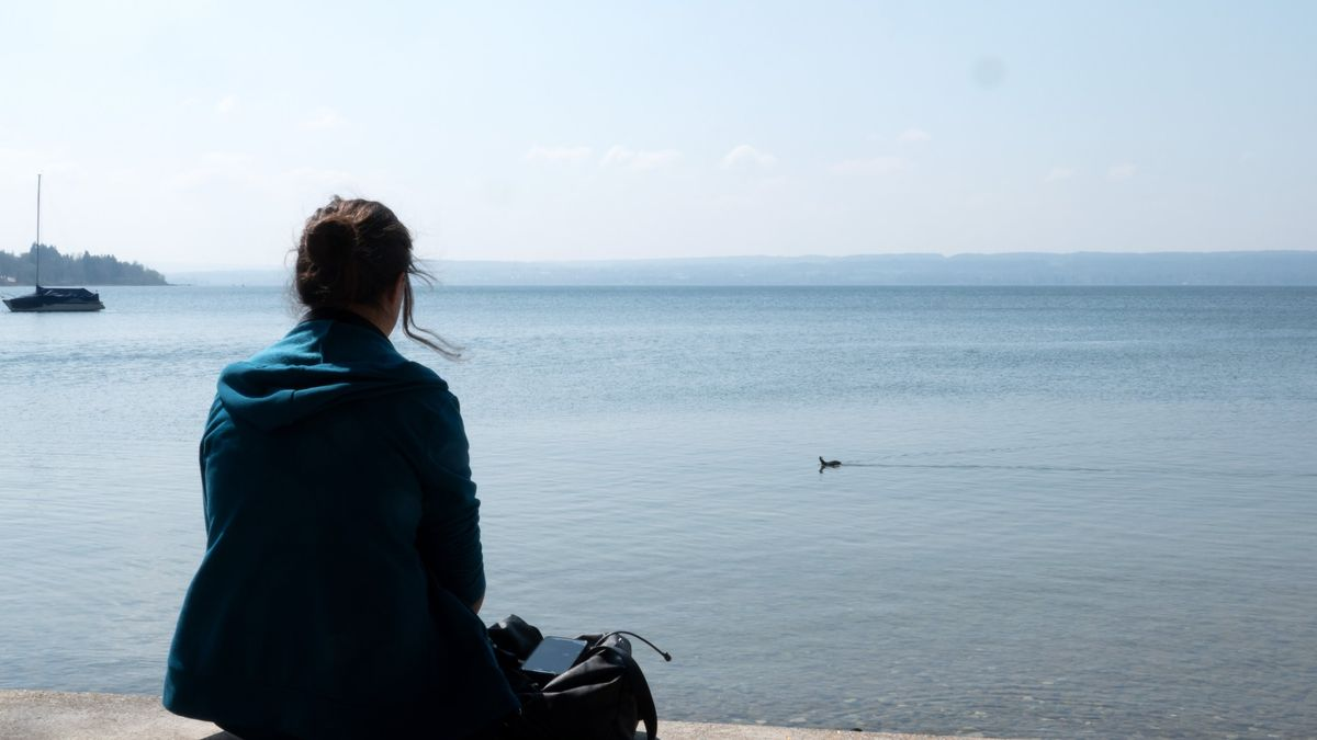 Eine Frau blickt nachdenklich auf einen stillen See.