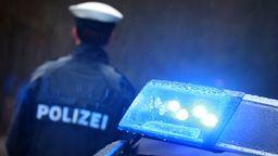 Ein Polizist steht im Regen vor einem Streifenwagen dessen Blaulicht aktiviert ist (Symbolbild) | Bild:dpa-Bildfunk/Karl-Josef Hildenbrand