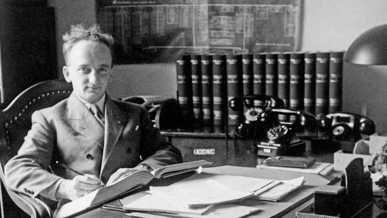 Der Chefankläger der Nürnberger Prozesse Benjamin Ferencz sitzt an einem Schreibtisch mit Papieren und drei alten schwarzen Telefonen (historische Schwarz-Weiß-Fotografie)