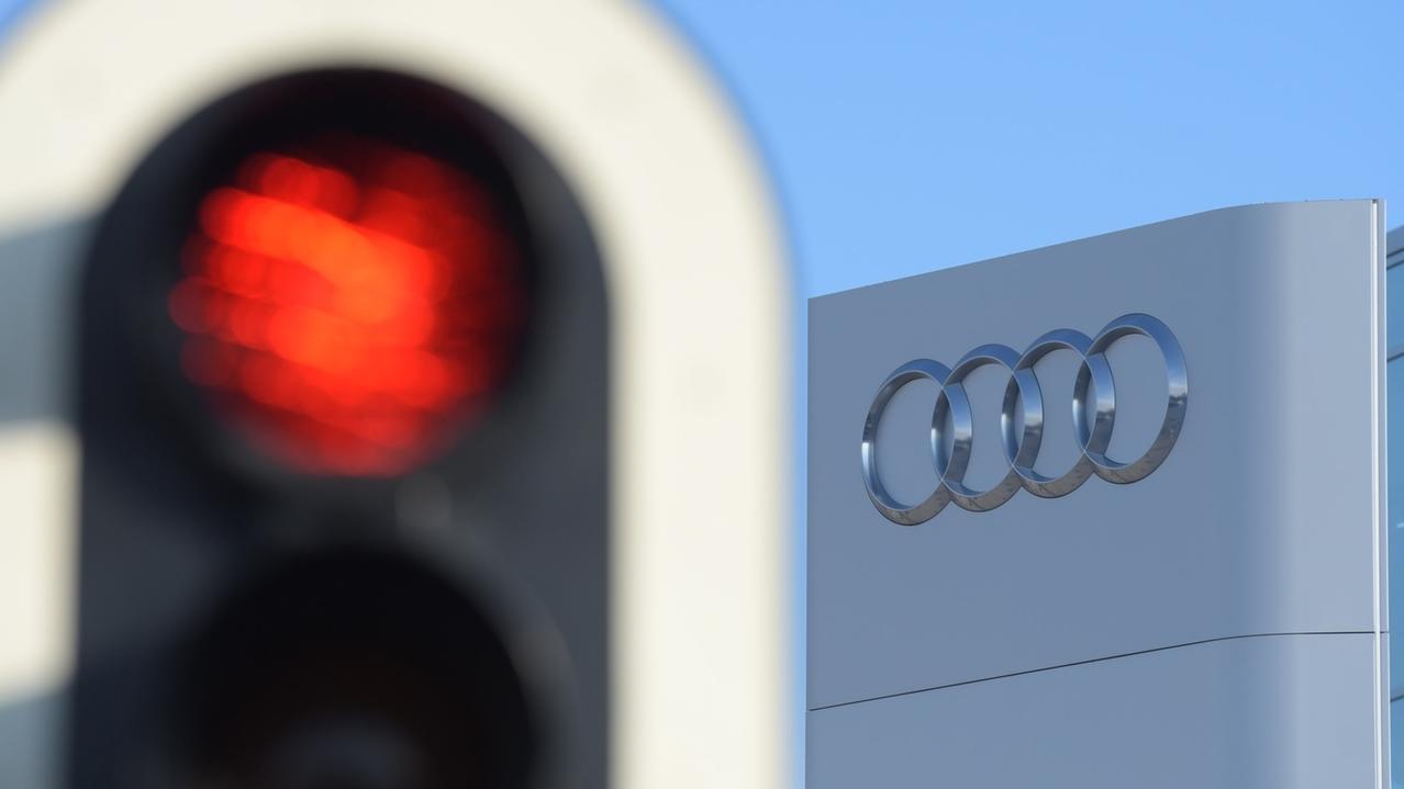 Eine Ampel leuchtet vor der Konzernzentrale des Autoherstellers Audi rot.