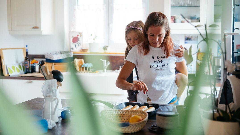 Eine Mutter kocht zusammen mit ihrer Tochter.