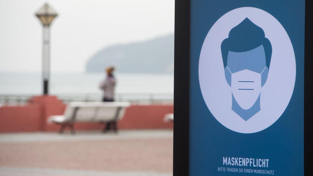 Ein Schild zur Maskenpflicht steht auf der Strandpromenade im Ostseebad auf der Insel Rügen.