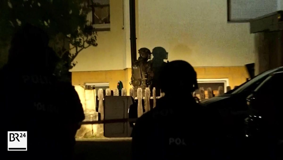 Bewaffnete Polizisten bewegen sich in der Nacht auf ein Haus zu.