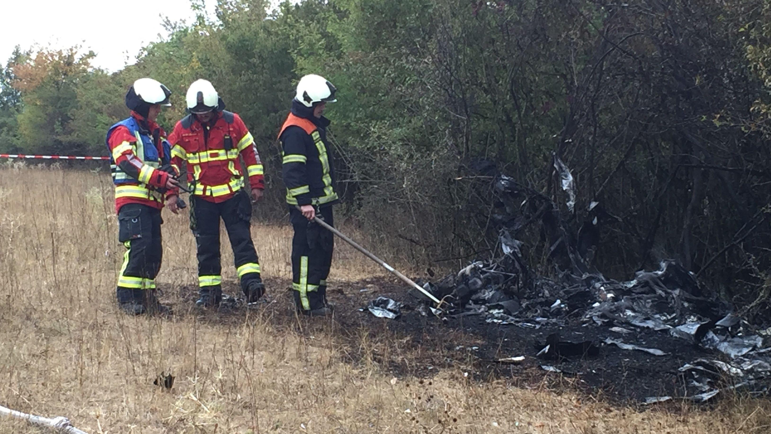 Feuerwehrleute vor den Resten eines Ultraleichtflugzeugs