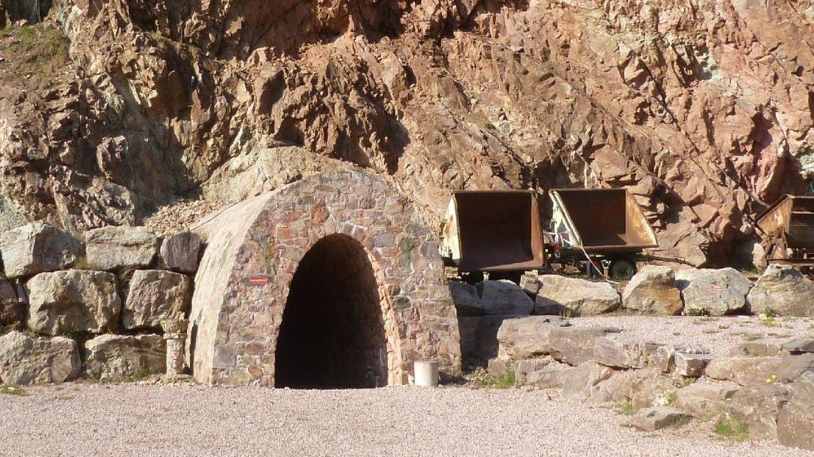 """Eingang zum Stollen der Grube """"Wilhelmine"""": ummauertes Stollenloch, daneben leere Loren"""