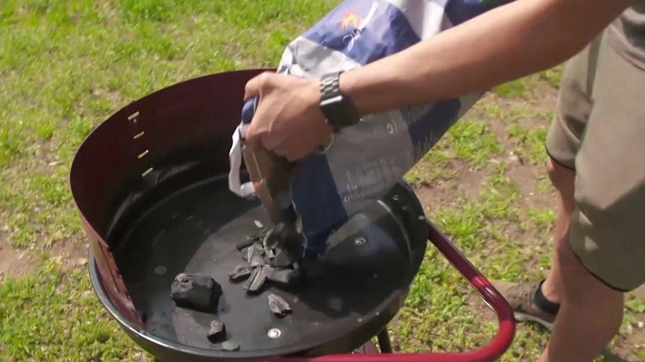 Kohle wird in einen Grill gefüllt