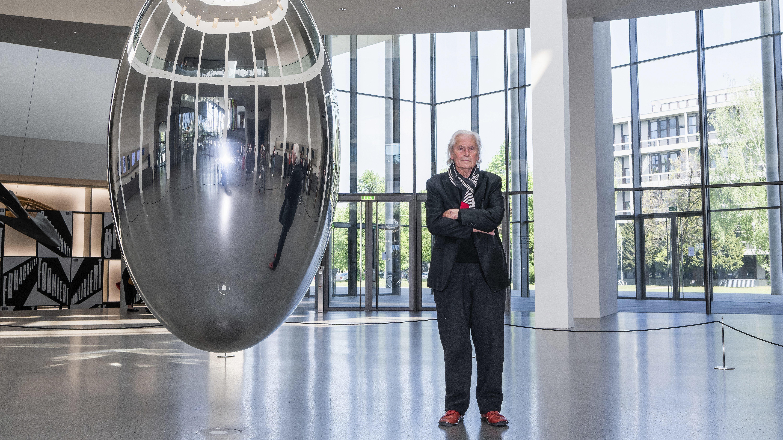 Ingo Maurer mit einem Kunstobjekt in der Pnakothek der Moderne.