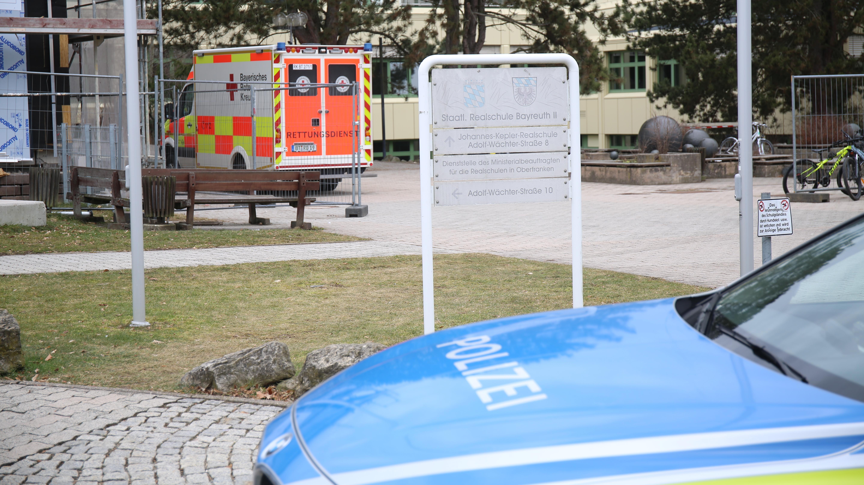 Fahrzeuge der Polizei und des Roten Kreuzes stehen vor einer Bayreuther Realschule.