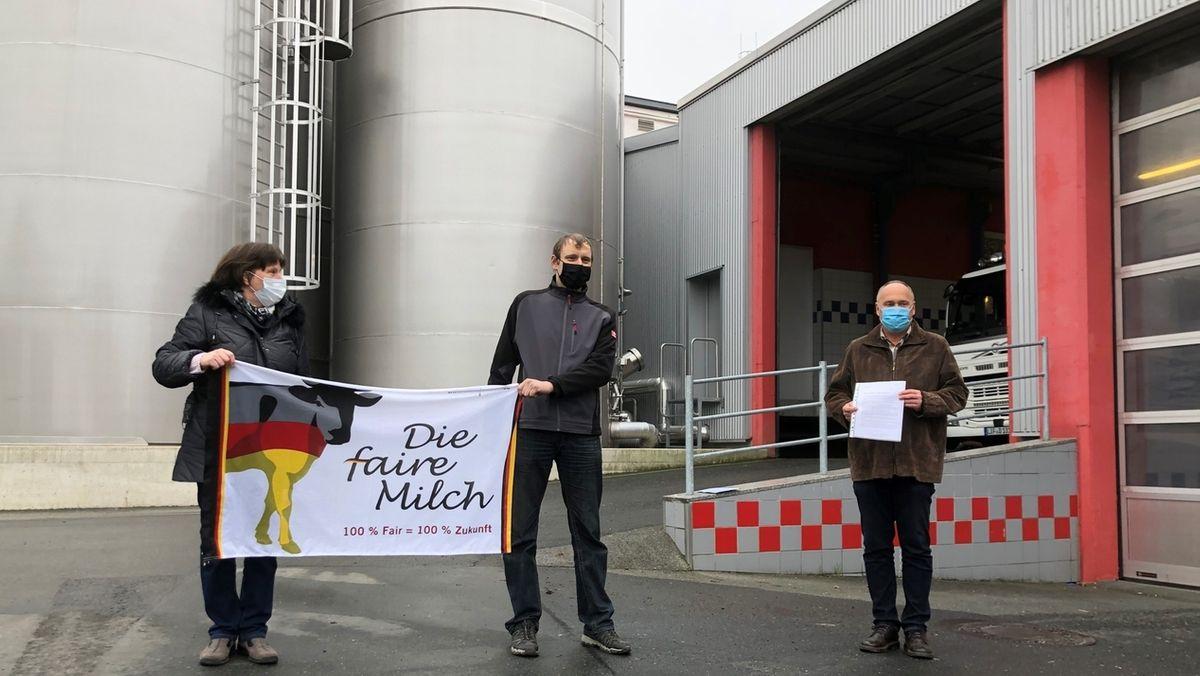 """Landwirte protestieren mit einem weißen Transparent vor einem Milchhof für höhere Preise. Auf dem Transparent ist eine Kuh abgebildet ist und ist der Schriftzug """"Die Faire Milch"""" zu lesen."""