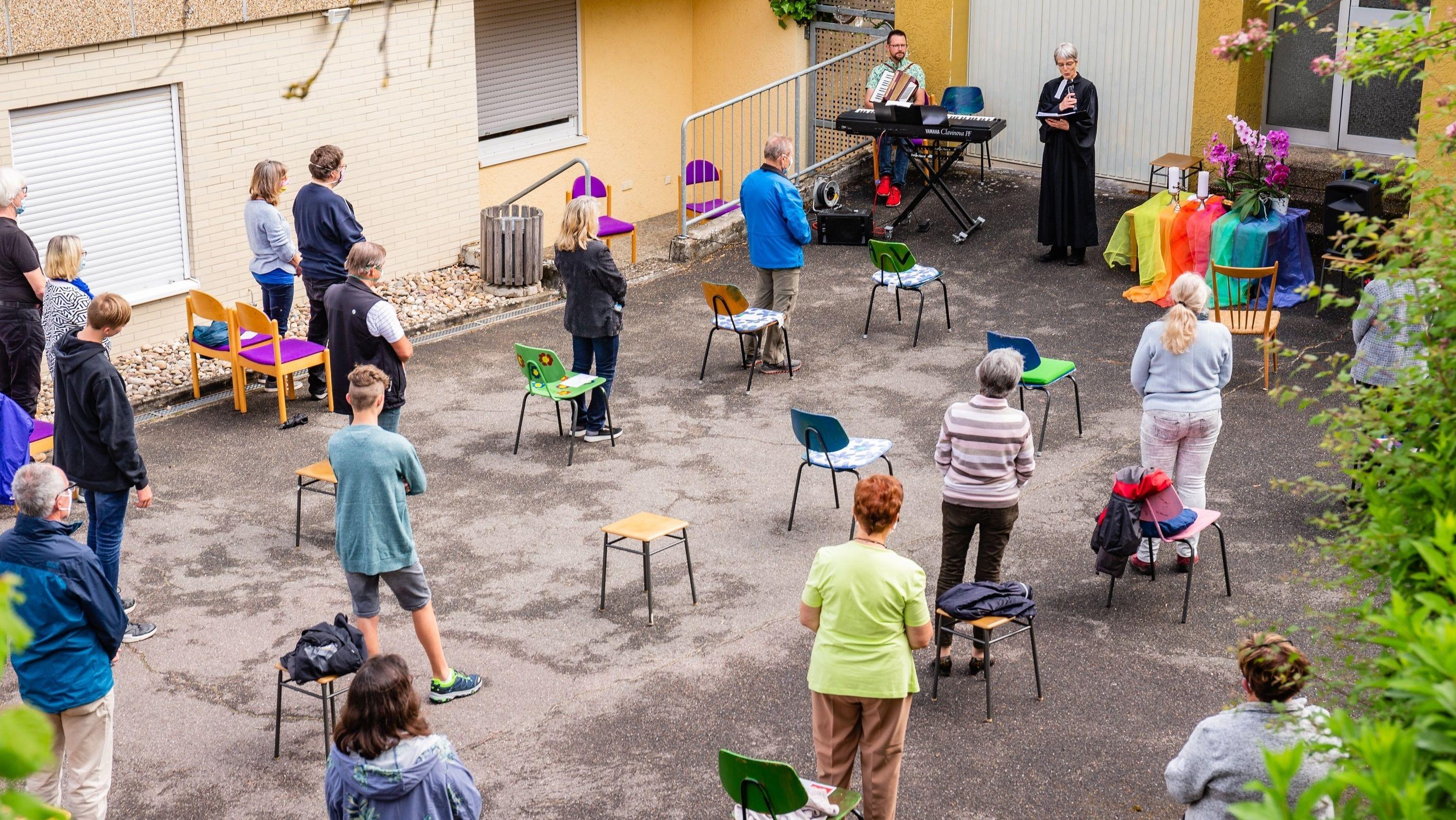 Ein Innenhof, in dem eine Pastorin einen Gottesdienst vor wenigen, auf mehrere Stühle verteilten Gläubigen abhält. Die Menschen stehen vor ihrem Stuhl und lauschen der Predigt