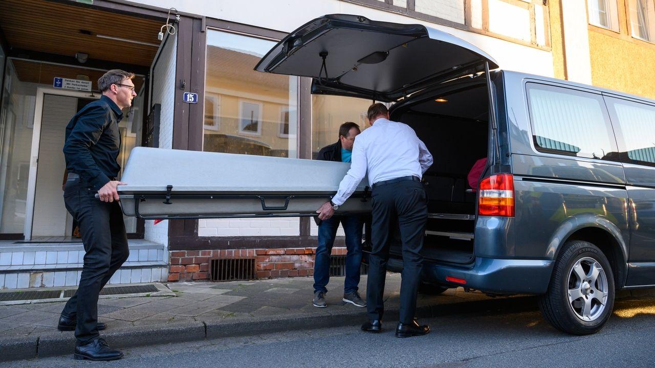 Bestatter schieben vor einem Haus einen Sarg in einen Leichenwagen.
