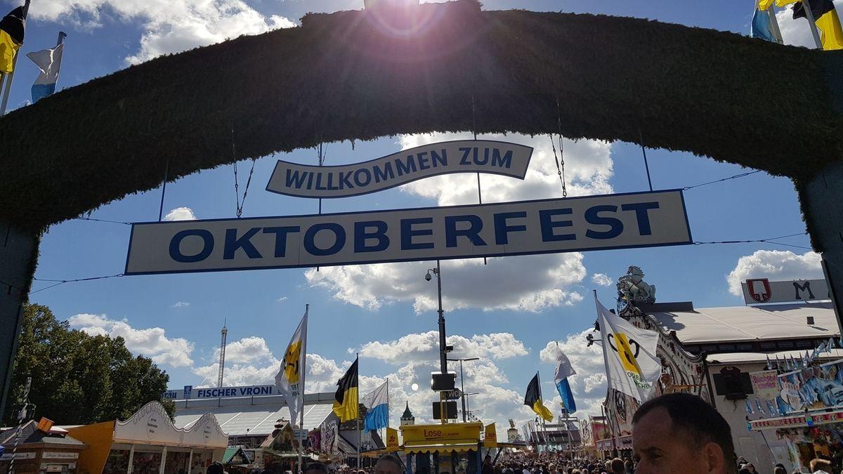 """Eingang zum Oktoberfest 2019: Im Eingangsbogen hängt der Schriftzug """"Willkommen zum Oktoberfest"""", durch den Bogen ein Blick aufs Oktoberfest, darüber blauer Himmel, Schönwetterwolken und die Sonne."""