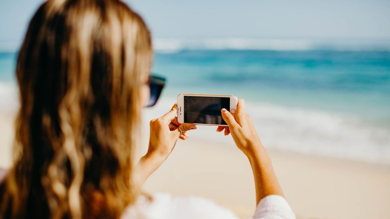 Eine Influencerin macht ein Foto am Strand
