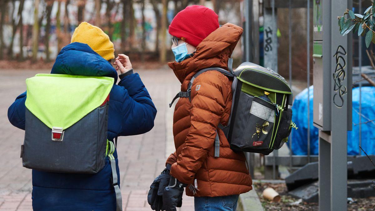 Zwei Schüler unterwegs mit Schulranzen und Maske
