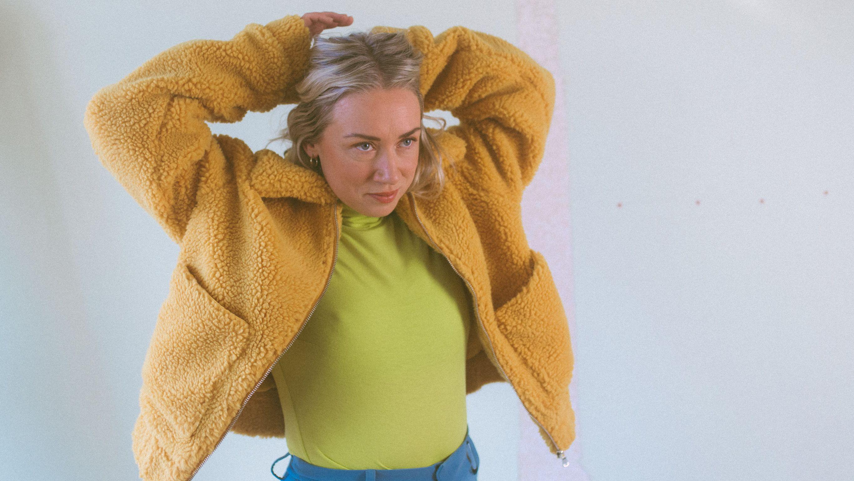 Musikerin Hanne Hukkelberg trägt eine gelbe Teddyjacke und einen lindgrünen Rollkragenpulli und verschränkt die Arme hinter dem Kopf