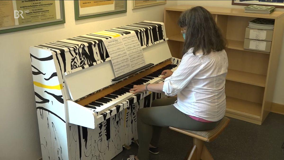 Eine Frau spielt auf einem Klavier.