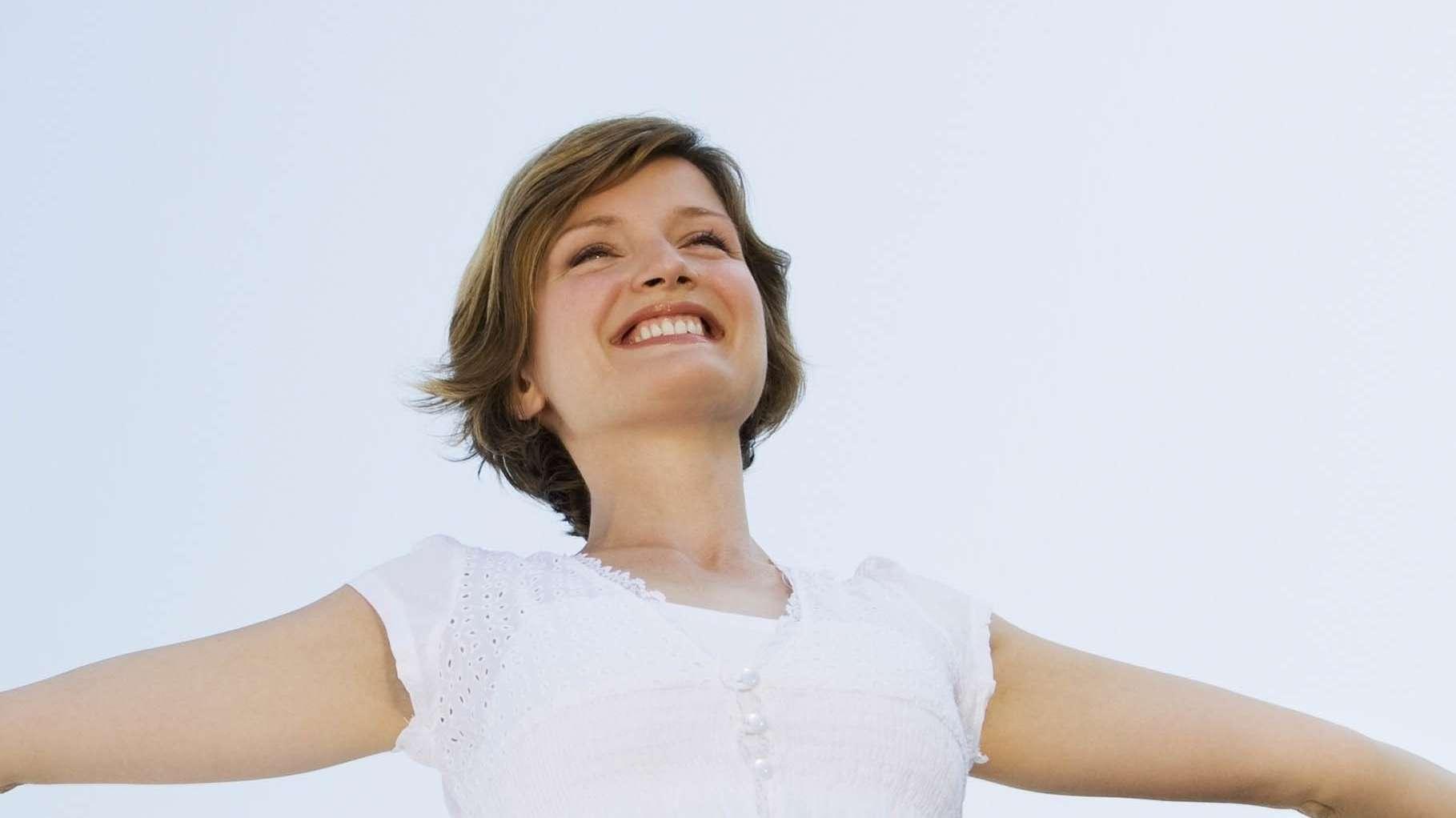 Mit ausgebreiteten Armen lächelnde Frau
