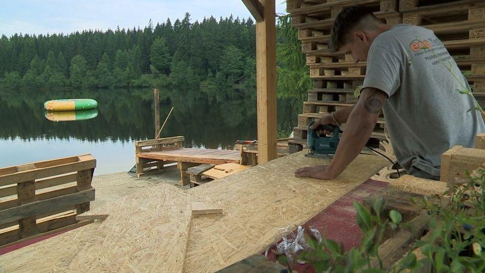Ein junger Mann bearbeitet eine Spanplatte in einer Bretterbude. Im Hintergrund ist ein See zu sehen.