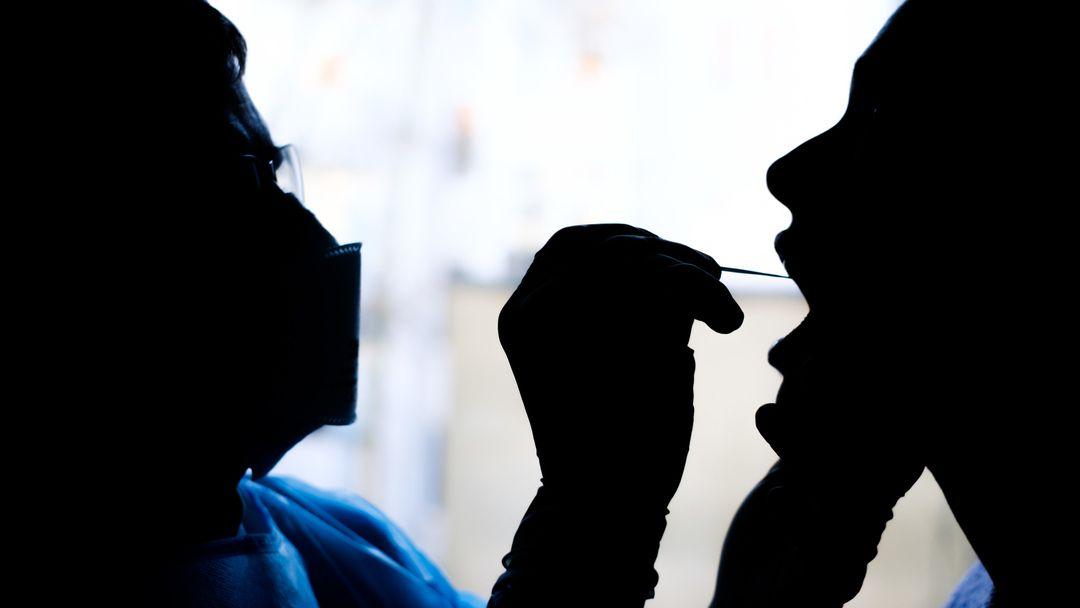 Ein Arzt nimmt bei einer Patientin einen Rachenabstrich für einen Covid-19-Schnelltest.