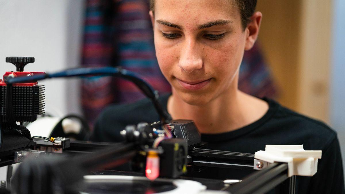 Schüler Bastian Steinlein kontrolliert die Einstellungen seines 3D-Druckers, während der Drucker neue Halterungen für Faceshields anfertigt.