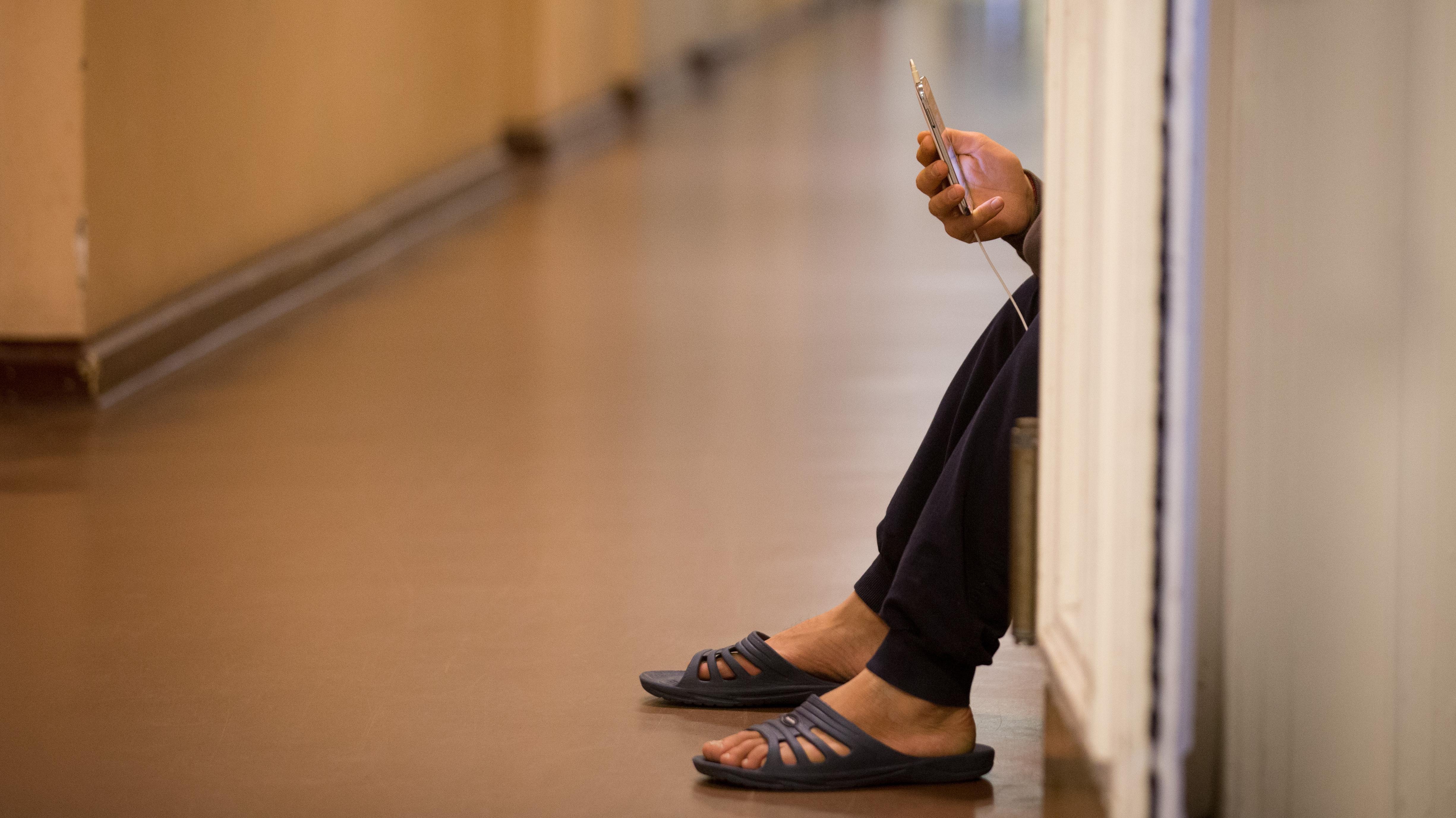 Ein in einem Gang hockender Flüchtling beschäftigt sich mit seinem Handy