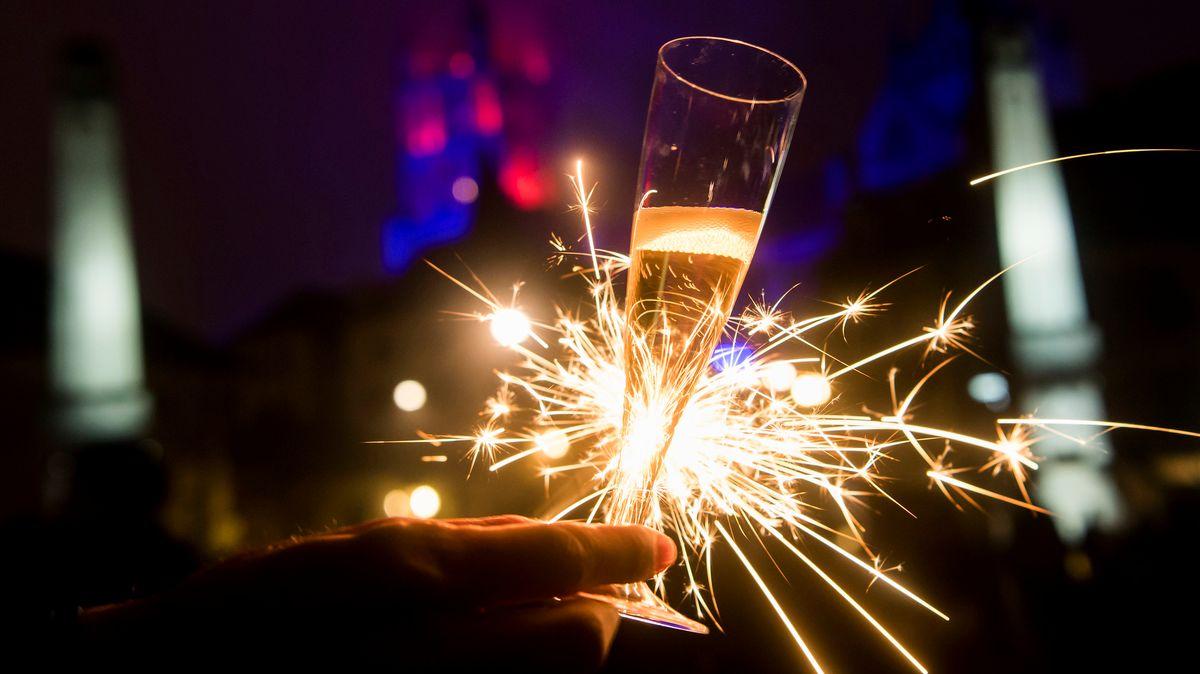 Eine Hand hält ein Glas, dahinter eine brennende Wunderkerze