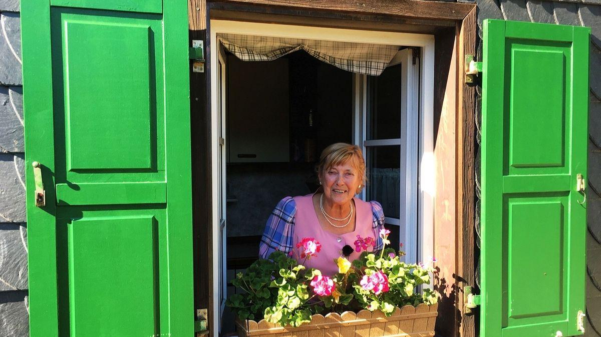Hüttenwirtin Hildegard Gleich im Dirndl schaut aus dem Fenster der Wanderhütte.