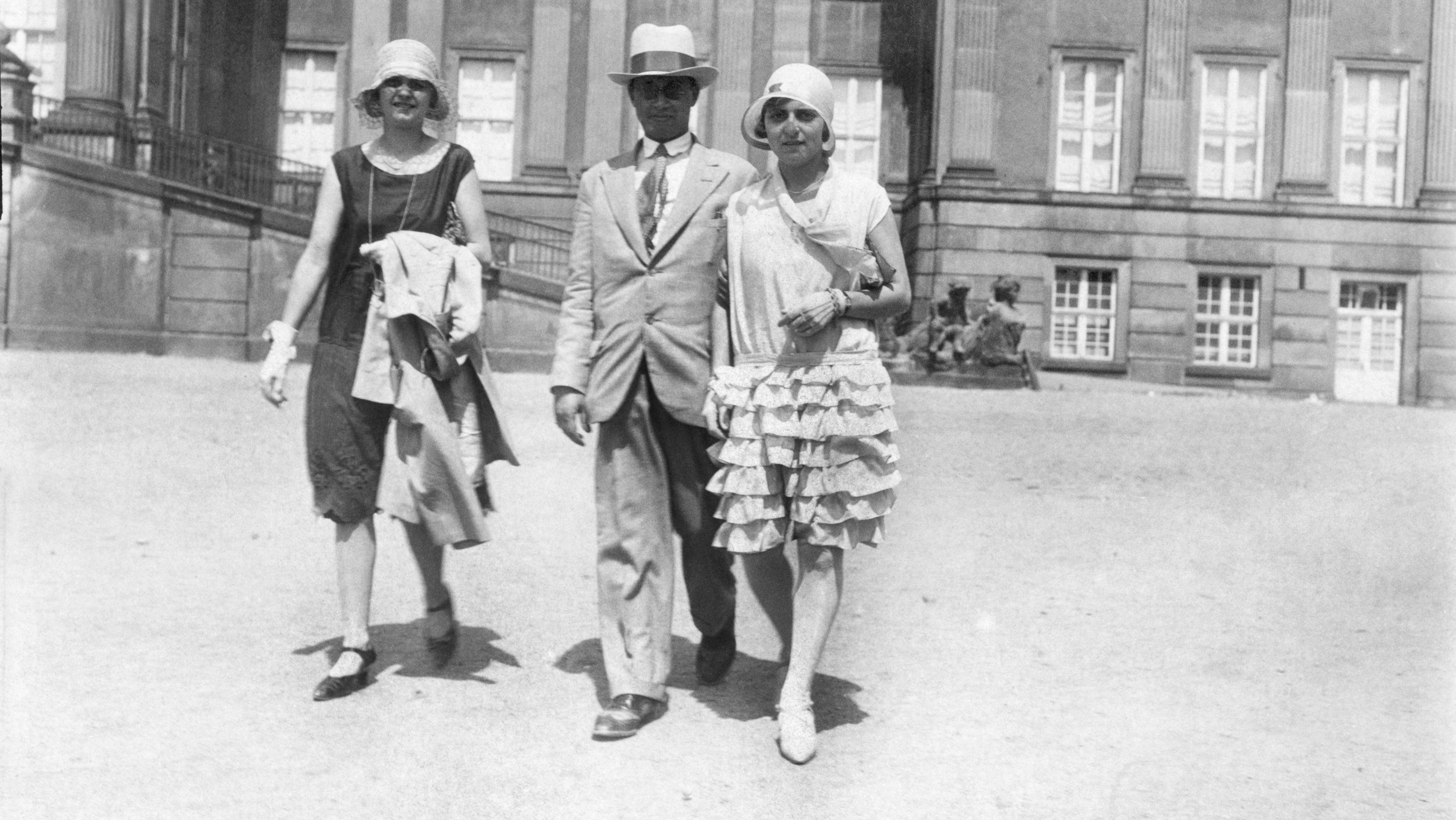 Ein historisches Schwarz-weiß-Foto von einem Mann und zwei Frauen, dir über einen Vorplatz laufen.