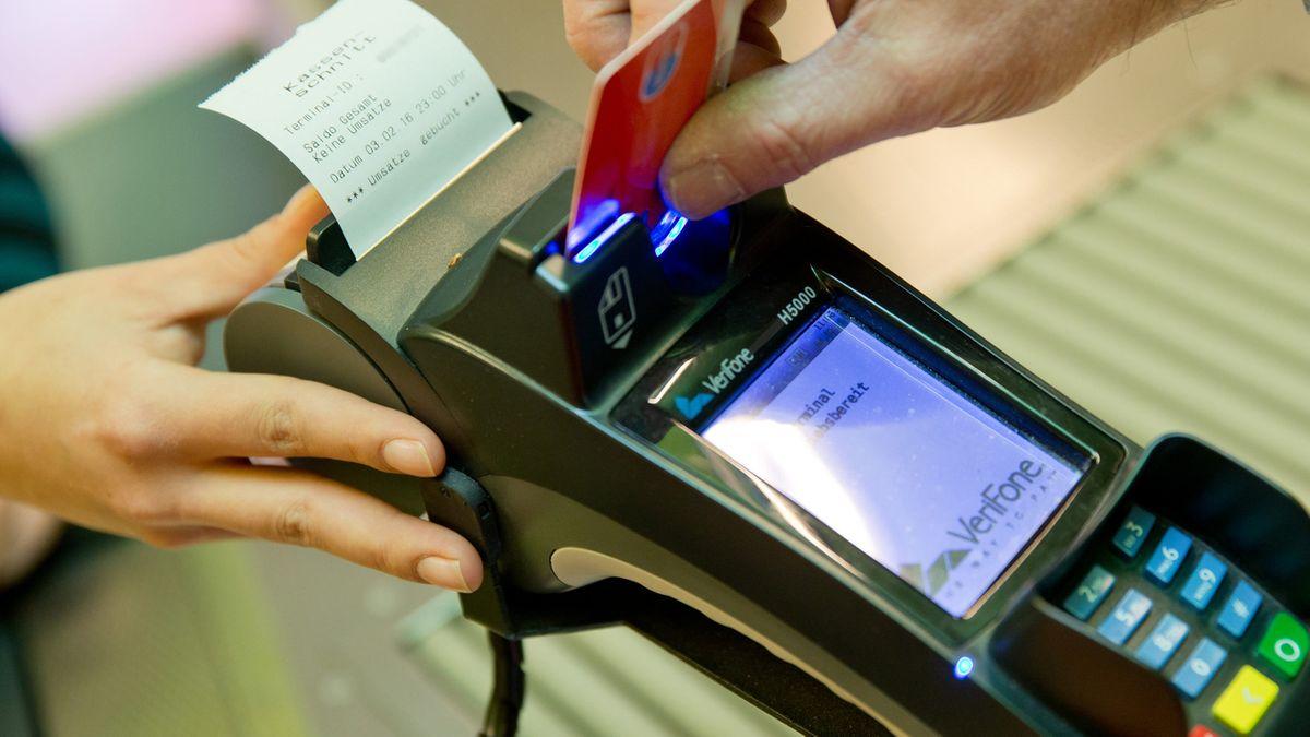 Nahaufnahme eines Zahlungsvorgangs in einem Geschäft. Ein Mann steckt seine EC-Karte in ein Kartenlesegerät