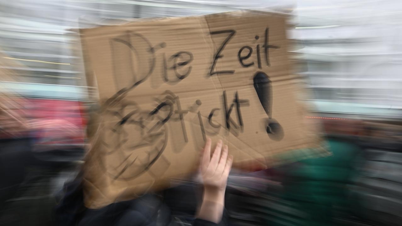 """Eine Schülerin läuft während einer Demonstration für den Klimaschutz mit einem Schild mit der Aufschrift """"Die Zeit tickt!"""" durch die Innenstadt."""