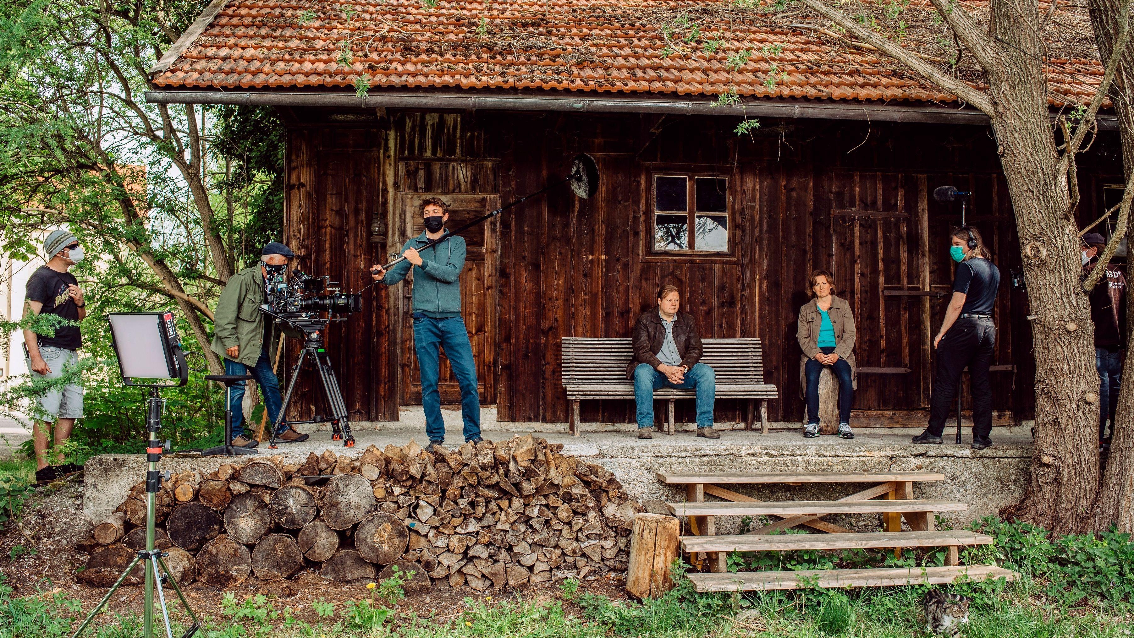 Szene vor einem Holzschuppen mit den Darstellern Michael A. Grimm und Senta Auth, die auf einer Bank und auf einem Hackstock sitzen