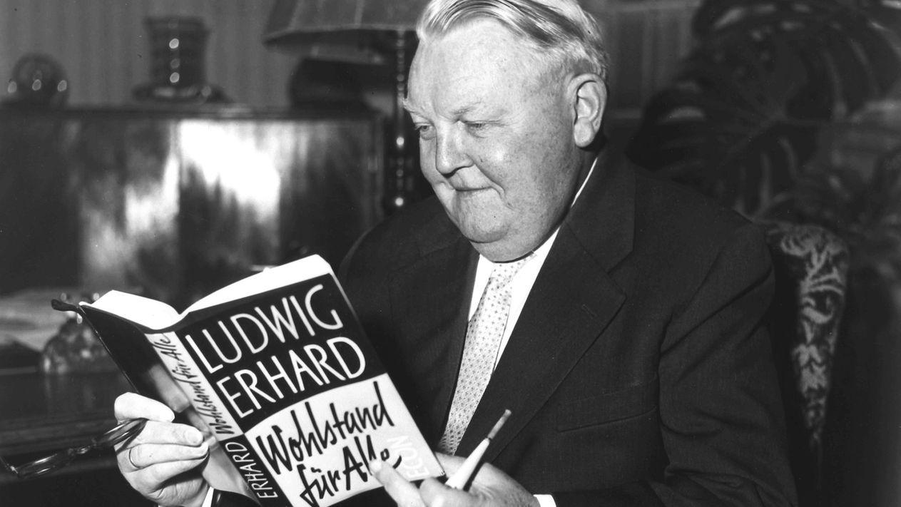 """Ludwig Erhard hält sein Buch """"Wohlstand für Alle"""" in der Hand"""