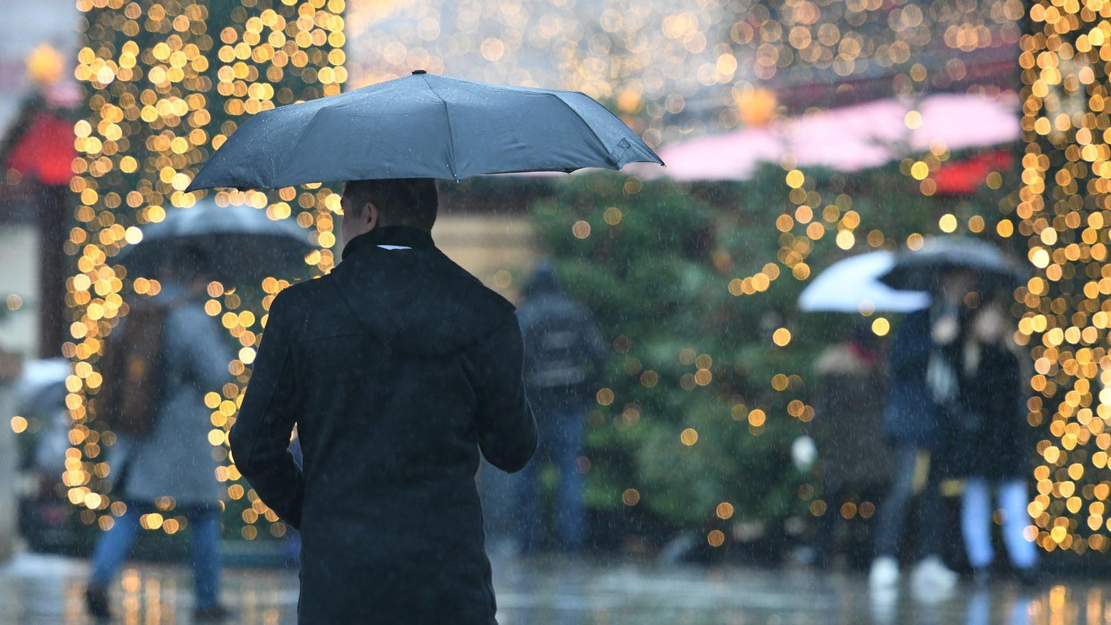 Nordrhein-Westfalen, Köln: Besucher gehen auf dem Weihnachtsmarkt am Dom mit Regenschirmen zwischen den Ständen hindurch.