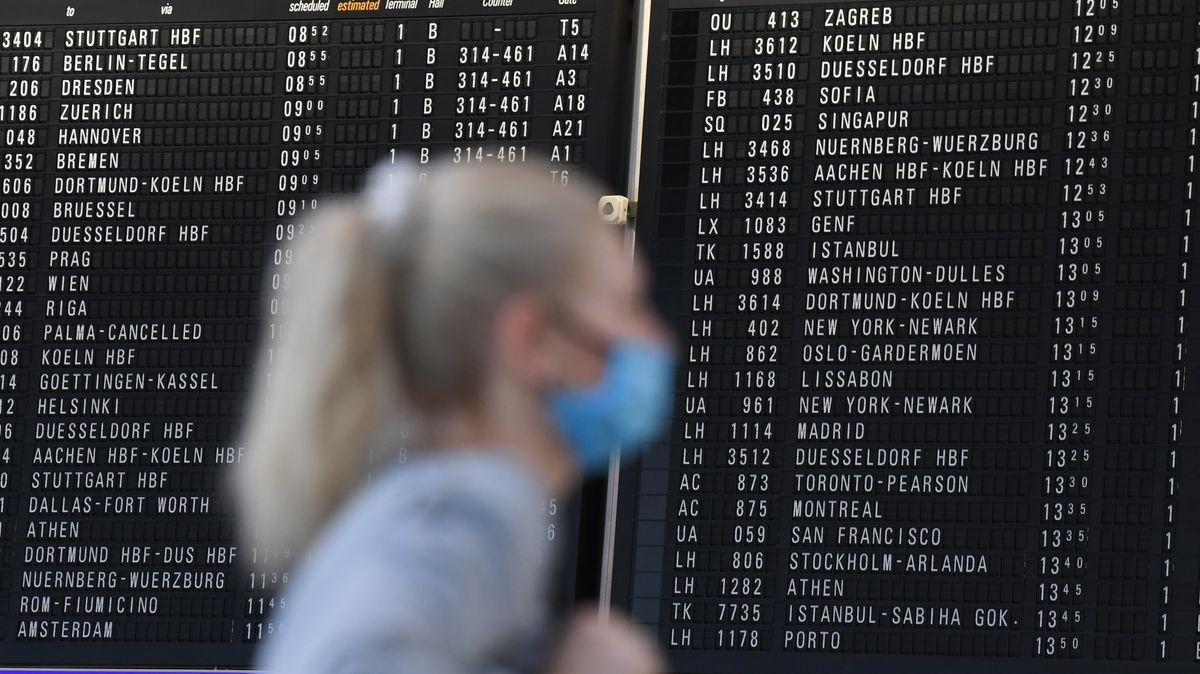 Eine Frau steht vor einer Anzeigetafel am Flughafen Frankfurt