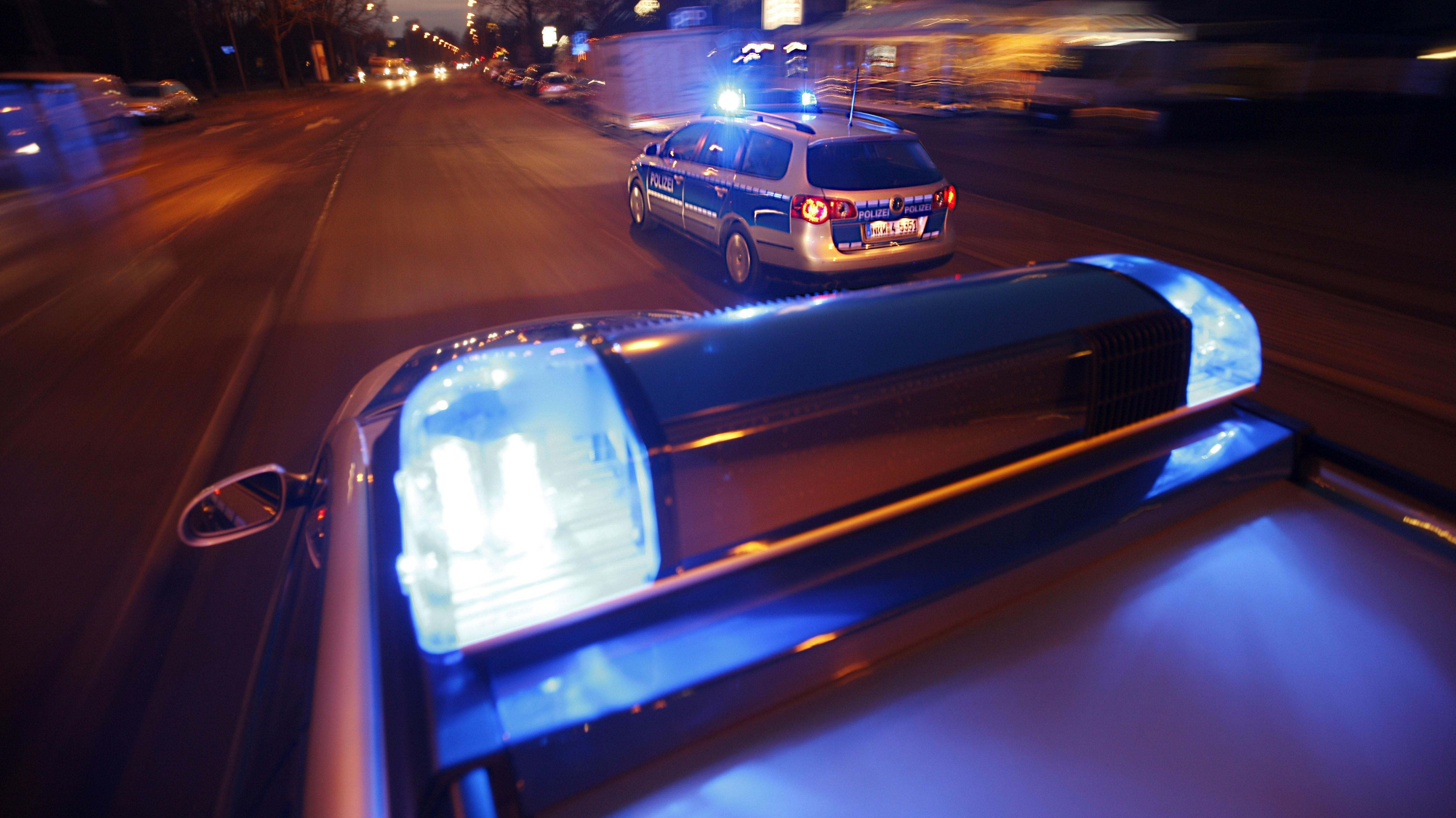 Polizeiautos fahren nachts mit Blaulicht durch eine Stadt