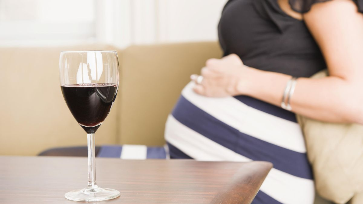 Glas Rotwein auf einem Tisch, schwangere Frau hinten