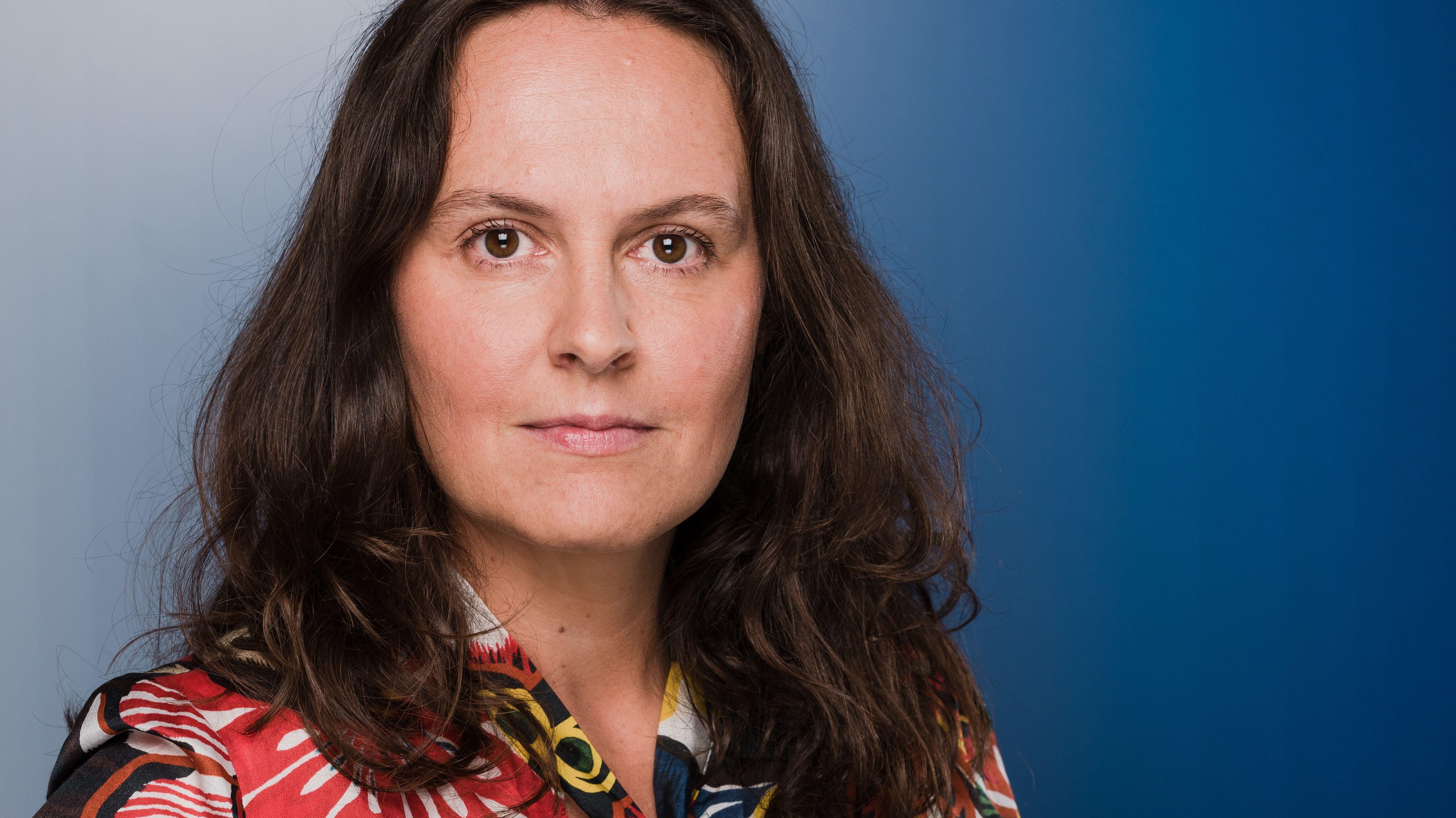 Autorin Jana Hensel blickt vor blauem Hintergrund in die Kamera