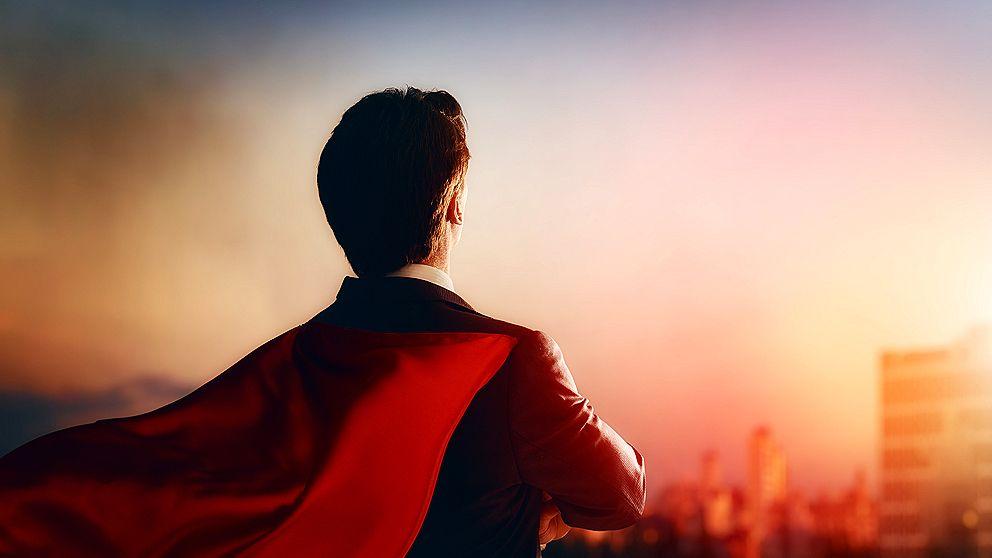 Mann von hintern, der rotes Cape trägt und in die Ferne schaut.